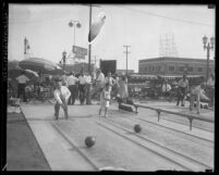 Outdoor bowling alley with bowlers against urban background in 1931; Los Angeles, Calif.