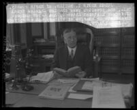 Judge Edwin I. Butler with book in hand, sitting at desk with shelves of law books behind him in Los Angeles, Calif., 1929