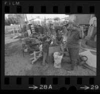 Barney Mull with two children at his Young People of Watts Improvement Center, mower repair yard in Watts, Calif., 1971