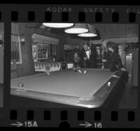 Actor Ryan O'Neal playing pool with three ladies at the Playboy Mansion in Los Angeles, Calif., 1971