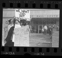 """Demonstrators, outside City Hall, holding up signs, one reading """"5% City Jobs in Not Enough!"""" at protest urging city to hire more Mexican Americans, Los Angeles, Calif., 1972"""