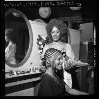 Hair stylist Cleo Jackson adding false braids to African American model in Los Angeles, Calif., 1972