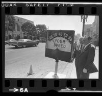 Mayor Sam Yorty and engineer S.S. Taylor demonstrating radar speed meter in Los Angeles, Calif., 1972