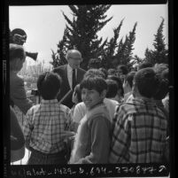 Composer-conductor Aaron Copland chatting with children following free Philharmonic concert for underprivileged youths in Los Angeles, Calif., 1972