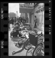 Demonstrators laying on sidewalk outside President Richard Nixon's Los Angeles campaign headquarters, 1972