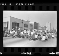 Anti-war demonstrators sitting across Wilshire Blvd. during protest in Los Angeles, Calif., 1972