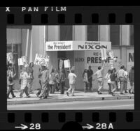 Pro-Nixon supporter picketing along side anti-war protesters outside Richard Nixon's Los Angeles campaign headquarters, 1972