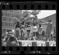 Gary Owens onstage with contestants in ape masks during Most Beautiful Ape contest in Century City, Calif., 1972