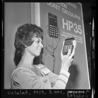 Julie Wright examining a Hewlett Packard HP35 pocket calculator at Wescon convention in Los Angeles, Calif., 1972