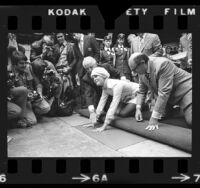 Actress Ali MacGraw placing her hand prints in cement at Chinese Theater in Hollywood, Calif., 1972