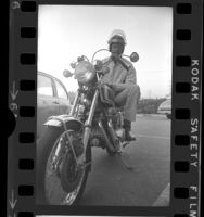 Basketball player and commentator Bill Russell seated on motorcycle in Los Angeles, Calif., 1973