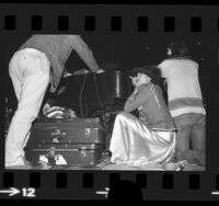 Bianca Jagger crouched behind piano at Rolling Stones concert to benefit Nicaragua in Los Angeles, Calif., 1973
