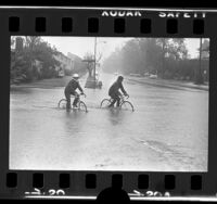 Two people riding bikes through flooded street in Sherman Oaks, Calif., 1973