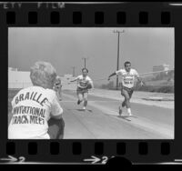 Two blind men training in the 100-yard dash for the Braille Institute Invitational Track Meet in Los Angeles, Calif., 1973