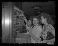 Three women tourists looking at post cards in Los Angeles' Union Station novelty shop, circa 1947