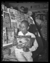 African American boy reading a Little Black Sambo book in a Los Angeles Drugstore, circa 1947