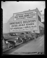 "Kelley Kar Company dealership, sign on side of building reads ""Attention! Veterans use your bond to buy a car"" in Los Angeles, Calif., 1947"