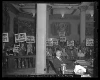 Protesters with signs in gallery of Los Angeles County Supervisors hearing over eminent domain for construction of Harbor Freeway, Calif., 1947