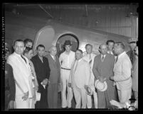 Howard Hughes and group of men standing beside airplane upon Hughes arrival in Los Angeles on August 2, 1938