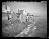 Five bathers running into ocean at Santa Monica Beach, circa 1947