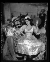 Noche de Carnival Queen Anita Aros with two people in papier-mâché masks at Olvera Street in Los Angeles, Calif., 1948