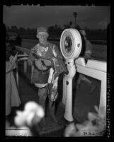 Jockey covered in mud standing on scale at Santa Anita Race Track in Arcadia, Calif., 1948