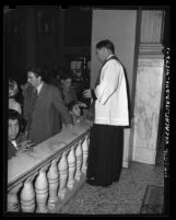 Father Paul Stroup giving sacrament on Ash Wednesday at St. Vibiana's Cathedral in Los Angeles, Calif., 1948