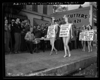 Earl Carroll's Vanities, chorus girls in costumes and wearing placards picketing Los Angeles Musicians Union Hall, 1938