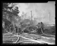 Firemen hosing down rubble and flames at Hillcrest Country Club explosion in Los Angeles, Calif., 1948