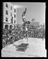 Mr. Muscles contestant performing acrobatic move as crowd watches at Muscle Beach in Santa Monica, Calif., 1948
