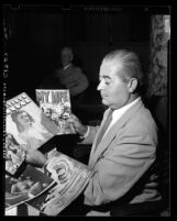 Councilman Ed J. Davenport displaying nude comic books in Los Angeles, 1948