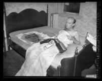 Edwin Gaffney covered with blanket and liquor bottles, reclining on mattress he set on fire at hotel in Los Angeles, Calif., 1948