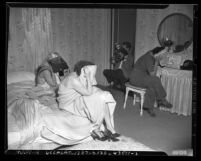 Three women covering their faces as photographer takes picture at raid on house of prostitution in Los Angeles, Calif., circa 1948