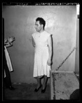 Sidney Cochin (aka The Nutty Housewife) wearing dress and heels in jail cell in Los Angeles, Calif., circa 1949