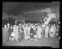 Group of Californians boarding airplane to visit Father Divine, 1949