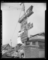 Elias Mushro adjusting price signage at National Auto Park lot, 1621 N. Hudson Avenue in Hollywood, Calif., 1949