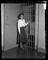 Dorothy Healey standing before jail cell in Los Angeles, Calif., 1949
