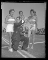 Man wearing gag thumb with three bathing beauties, Long Beach, Calif., 1949