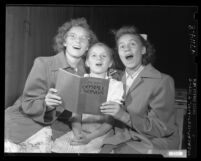 "Laura, Ruth, and Lillian Wozniuk with ""Phil Kerr's Gospel Songs"" book at tent revival in Los Angeles, Calif., 1949"
