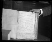 "Man's hand holding open charter of 1850 to page declaring that ""Pueblo de Los Angelos"" will be known as ""City of Los Angeles"";"