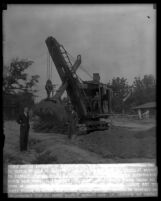 Three officials from California Institute of Technology posing with a steam shovel at 1930 groundbreaking ceremonies for dormitories