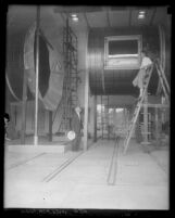 Dr. Clark B. Millikan on ladder looking into Caltech wind tunnel while another man observes from below in Pasadena, Calif., 1929