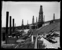 Scattered wells in oil field with three men looking down on tanks in Montebello, Calif., circa 1920