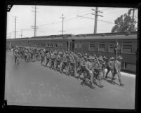 160th Infantry of California National Guard marching besides train in Los Angeles, Calif., 1924