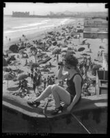 Woman with spy glass looking out from Santa Monica pier with crowded beach in background, Calif., circa 1920