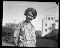 1/2 length portrait of Nita Carson standing on street smiling in Los Angeles, Calif., 1925