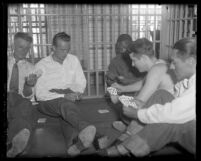 Murder suspect David H. Clark playing cards with other prisoners in jail cell in Los Angeles, Calif., 1931