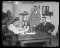 Los Angeles prohibition enforcement officer George Contreras sitting at his desk, with two other unidentified men, circa 1920