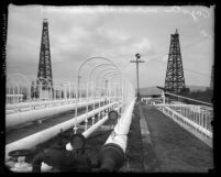 Pipeworks and oil well towers in the Los Angeles County, Calif. Coyote oil fields, circa 1920