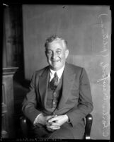 Portrait of Charles H. Crawford smiling, while seated with hands in lap, circa 1930